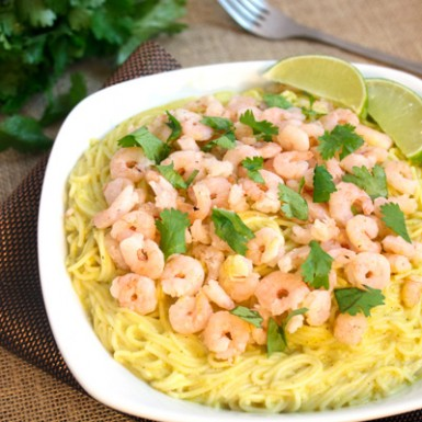 a white plate filled with angel hair pasta topped with shrimp in a creamy curry sauce. Garnisged with cilantro and lime slices.