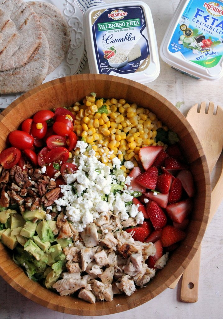 a large wooden bowl filled with salad covered in sections of strawberries, avocado, feta, corn, and nuts