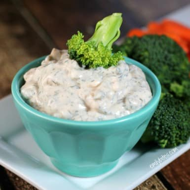 Creamy Dill Dip in a blue bowl with broccoli florets