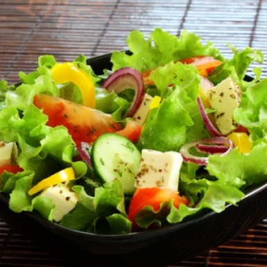 Light Italian Dressing on a salad with greens, cucumbers, and peppers, and onions