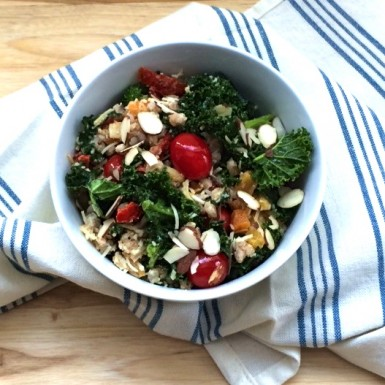 a white bowl filled with a kale, broccoli, and farro salad