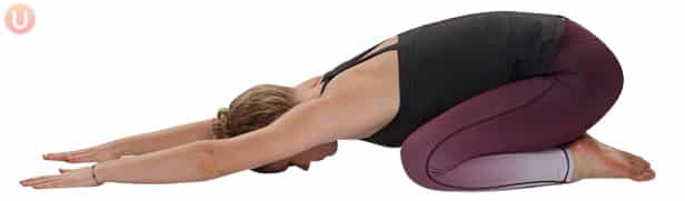 Chloe Freytag demonstrating Child's Pose in a back tank top and purple pants