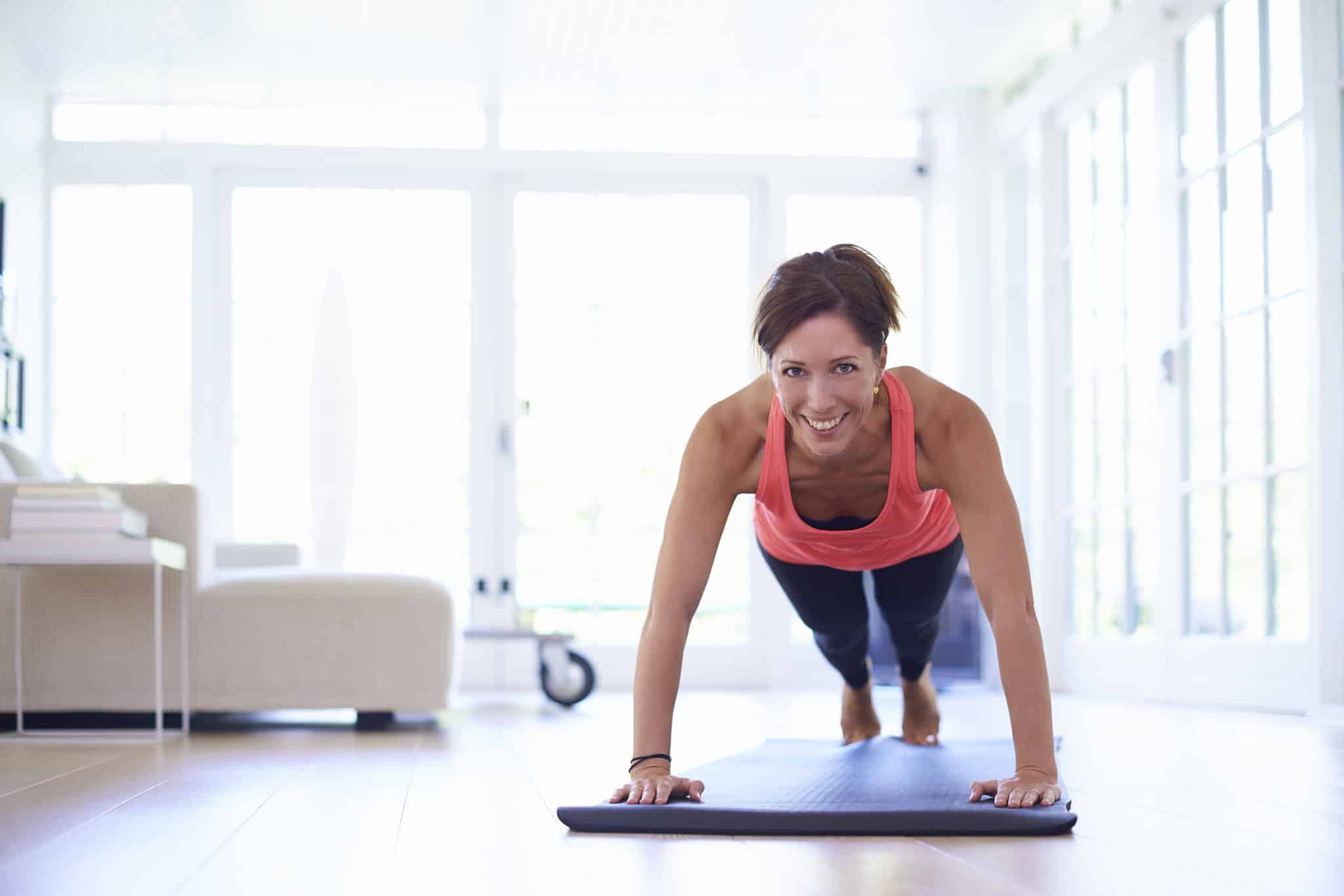 Mid adult woman doing press ups in living room