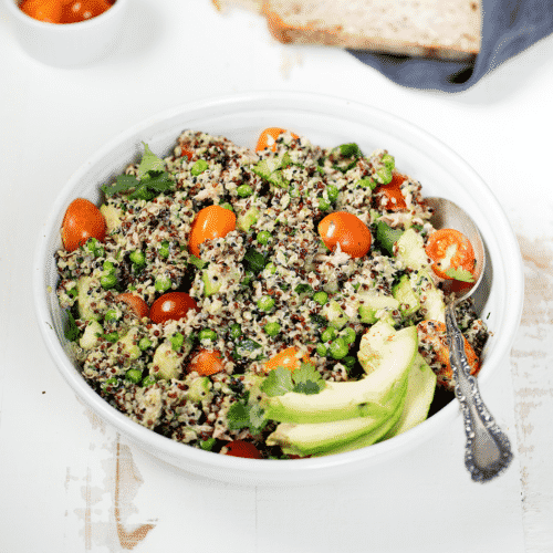 This is a photo of a bowl of Green Goddess Tuna Quinoa Salad that is a healthy, protein-packed, gluten-free salad full of Spring Veggies, tuna, quinoa and a delicious dressing!